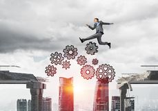 Problem and difficulties overcoming concept. Businessman jumping over gap with gear mechanism in concrete bridge as symbol of overcoming challenges. Cityscape Stock Images