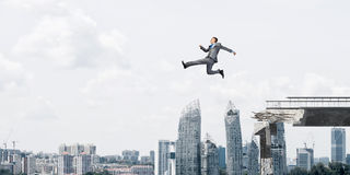 Problem and difficulties overcoming concept. Businessman jumping over huge gap in concrete bridge as symbol of overcoming challenges. Cityscape on background Royalty Free Stock Photography