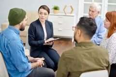 Problem Discussion at Group Therapy Session. Group therapy session at full speed: confident young psychologist discussing problem with patient and taking notes stock photos