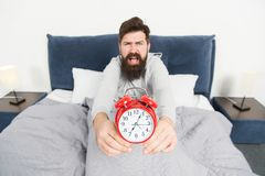 Problem early morning awakening. Get up with alarm clock. Overslept again. Tips for waking up early. Man bearded sleepy stock image