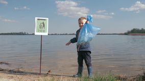 Problem ecological pollution litter in nature, portrait of little boy with garbage bag in hand after cleaning up plastic stock video