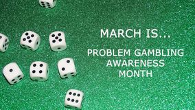Problem gambling awareness month. Is March. Sign with dice and green glitter background Royalty Free Stock Images