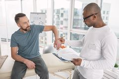 Pleasant bearded man showing his arm. Problem with muscles. Pleasant bearded men looking at his doctor while showing his arm Stock Images