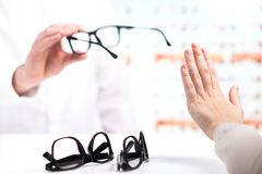 Problem at optician. Unhappy customer refuse to try. stock photography