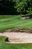 Problem på golfbanan, sandfälla som skyddar en golfgräsplan med träd i bakgrunden, inkluderar stiftet med den röda flaggan och go arkivfoton
