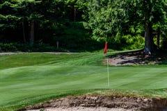 Problem på golfbanan, sandfälla som skyddar en golfgräsplan med träd i bakgrunden, inkluderar stiftet med den röda flaggan och go royaltyfria foton