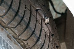Punctured tire by bolt stock image