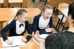 Children laugh at the school teacher. The problem of raising children in school. The authority of the teacher has fallen. Schoolgirl girls laugh at the words of royalty free stock image