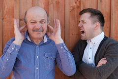 Problem in relations between generations. Young men shouts on his father-in-law Stock Images
