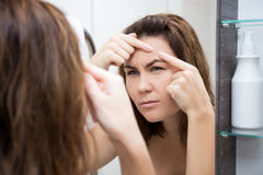 Problem skin concept - sad woman looking at mirror Royalty Free Stock Photos