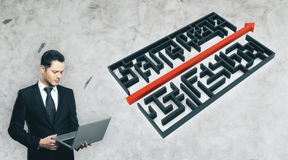Problem solution concept. Businessman using laptop next to abstract maze with arrow on concrete background. Problem solution concept Royalty Free Stock Photography