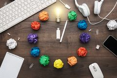 Top view of an office table with great idea concept. problem solution concept depicted by colorful crumpled paper and light bulb. Flat lay composition with royalty free stock photo