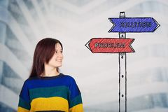 Problem solution. Young woman looking at a road sign sketch with solution and problem arrows showing to right and left side. Life choice, challenge and decision stock photo