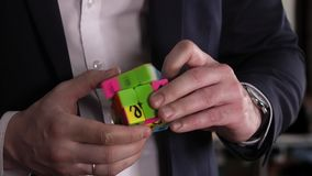 Problem and solve . Businessman hands solving Rubik`s cube puzzle in the office. stock video