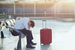 Problem with transportation, delay of flight in airport. Problem with transportation, delay of flight, depressed commuter with his luggage Stock Photo
