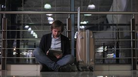 Problem with transportation, delay of flight, depressed man with his luggage and tablet, headache and red eyes. Problem with transportation, delay of flight stock video