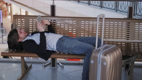 Problem with transportation, delay of flight, depressed man with his luggage and tablet, headache and red eyes. Problem with transportation, delay of flight stock footage