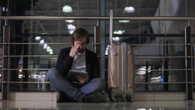 Problem with transportation, delay of flight, depressed man  his luggage and tablet, headache  red eyes. Problem with transportation, delay of flight, depressed Royalty Free Stock Images