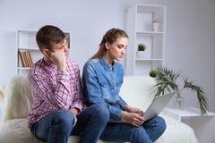 Problem w parze Wzburzony m??czyzny obsiadanie na kanapie blisko jego kobiety dopatrywania laptopu zdjęcie stock