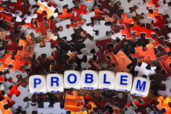 Problem Word. Dice spelling out the word problem sits on top of red and gray scattered puzzle pieces Royalty Free Stock Photo