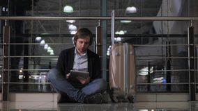 Problema con trasporto, il ritardo del volo, l'uomo depresso i suoi bagagli e la compressa, occhi rossi di emicrania Fotografia Stock