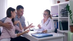 Problema da infertilidade, doutor fêmea que fala ao casal da virada sobre o diagnóstico desfavorável no escritório médico vídeos de arquivo