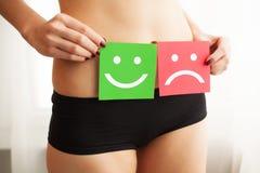 Problema de saúde da mulher Close up da fêmea com corpo magro apto na cuecas que guarda o cartão dois com Smiley And Happy Face t fotos de stock