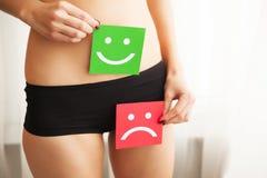 Problema de saúde da mulher Close up da fêmea com corpo magro apto na cuecas que guarda o cartão dois com Smiley And Happy Face t imagens de stock royalty free