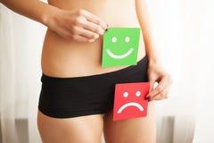 Problema de saúde da mulher Close up da fêmea com corpo magro apto na cuecas que guarda o cartão dois com Smiley And Happy Face t fotos de stock royalty free