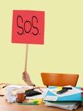 Problema del lavoro, lavoro eccessivo ecc Il SOS cede firmando un documento lo scrittorio disordinato sudicio Fotografia Stock