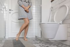 Problema della donna che tiene le sue mani nella toilette immagine stock