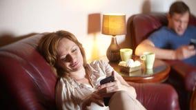 Problema di comunicazione ed interno nella famiglia il marito e la moglie utilizzano il loro smartphone, trascurantesi fotografia stock