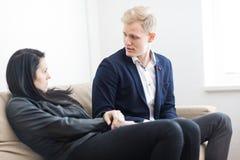 Problema di disputa delle giovani coppie mentre sedendosi sul sofà immagini stock libere da diritti