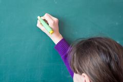 Problema di scrittura della ragazza della scuola elementare sul bordo Fotografie Stock