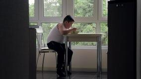 Problema do conceito do excesso de peso e da obesidade nas crianças o menino gordo está sentando-se em uma tabela que olha para f vídeos de arquivo