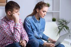 Problema nelle coppie Uomo turbato che si siede su un sof? vicino al suo computer portatile di sorveglianza della donna fotografia stock libera da diritti