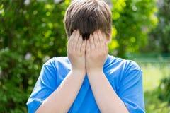 Problemas adolescentes - el muchacho cubrió su cara con sus manos afuera Imágenes de archivo libres de regalías