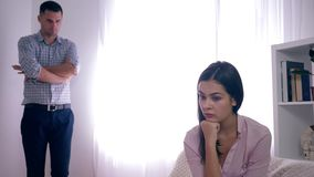 Problemas da família, mulher virada frustrados após a discussão com o homem em fundo unfocused na sala brilhante vídeos de arquivo