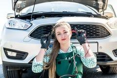 Problemas de búsqueda del mecánico de la mujer con el motor de coche fotografía de archivo