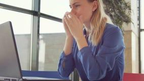 Problemas de la alergia y de salud para la mujer joven que estornuda en oficina mientras que usa el ordenador portátil almacen de metraje de vídeo