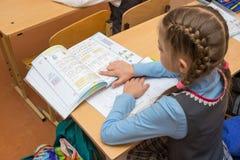 Problemas de la condición de la lectura de la colegiala en el libro de texto Imagen de archivo libre de regalías