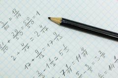 Problemas de matemática no papel de gráfico com lápis preto imagens de stock