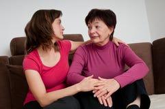 Problemas grandes - la hija conforta a la madre mayor foto de archivo