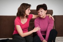 Problemas grandes - la hija conforta a la madre mayor imagenes de archivo