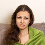 Problemas psicológicos de las adolescencias Mujer joven deprimida que se sienta en el sofá La muchacha adolescente subrayada y tr Foto de archivo