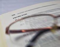 Probleme auf einem Schul- und Hochschullehrbuch mit Gläsern Lizenzfreies Stockbild