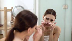 Problemhaut Frau, die Stelle auf Gesicht zerquetscht und im Spiegel schaut stock footage