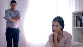 Problemi della famiglia, donna turbata frustrati dopo il litigio con il maschio su fondo unfocused nella stanza luminosa video d archivio
