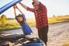 Problemi della riparazione della figlia e del padre con l'automobile durante il viaggio stradale di estate immagini stock