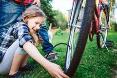Problemi della riparazione della figlia e del padre con la bicicletta all'aperto di estate immagine stock libera da diritti